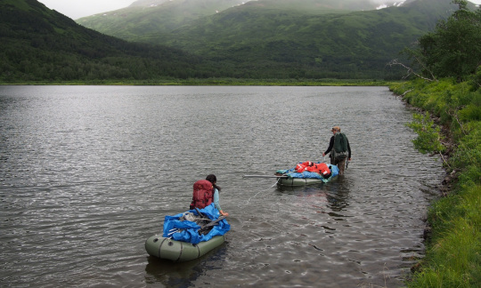 Two people pull two rafts on a river with foggy mountains in the background.