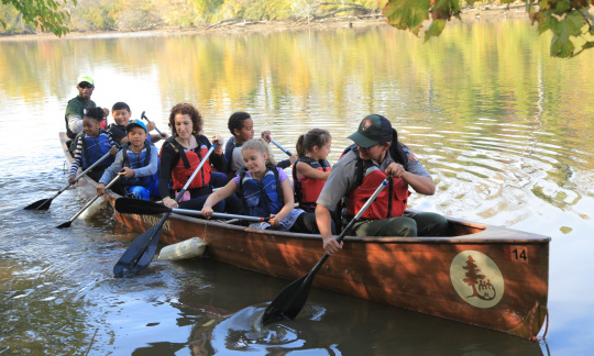 A group of kids and two adults paddle a large canoe on a calm stream.