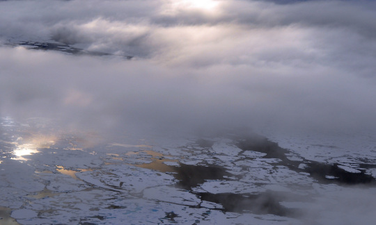 Clouds drift in beams of sunlight above large icebergs floating on the ocean.