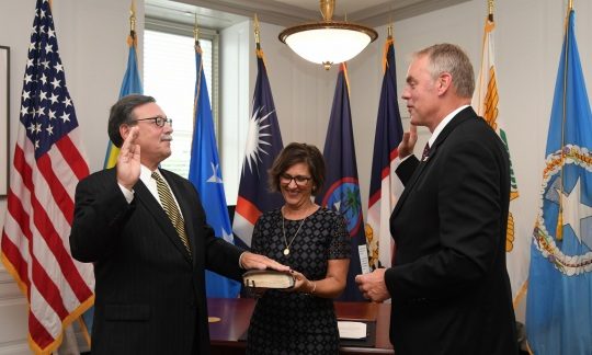 Doug Domenech, a caucasian man with graying hair and glasses, wears a suit and raises his hand as he is sworn in by Secretary Zinke, a tall caucasian man with gray hair and a suit.