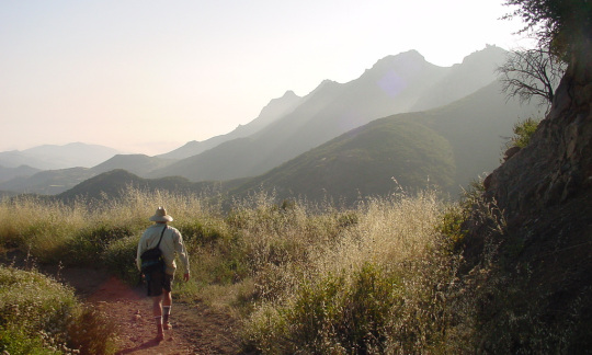A man is walking away from the camera on a dirt trail leading to mountains in the distance.