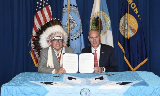 Secretary Zinke signs agreement with Blackfeet Nation Chairman Harry Barnes in front of flags