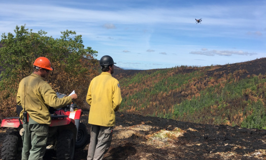 Two men in yellow shirts and hard hats stand on a recently burned hilltop next to a four wheel ATV and use a remote control to fly a small drone over a forest.