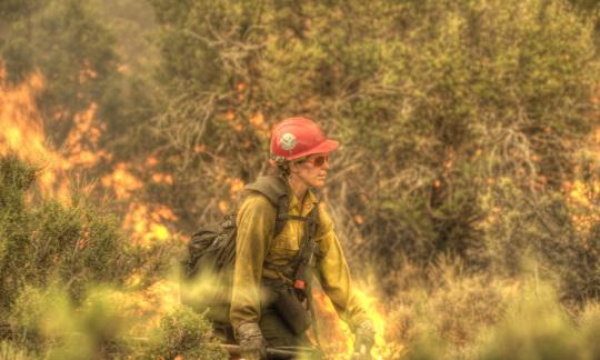 A female wild land firefighter walks by a fire in Oregon.
