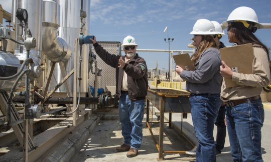 A small group of people wearing hard hats inspects a large installation of pipes in an outdoor oil and gas facility.