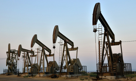 A line of five pumpjacks stand on a grassy plain.