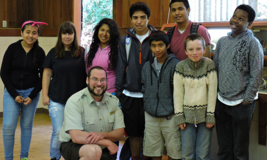A small group of young students poses in a classroom with a large white man in a BLM uniform.