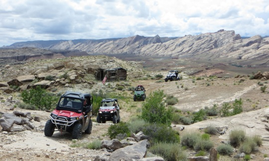 Four all terrain vehicles drive on a dirt path through a rocky desert valley with small plants scattered around and sloping hills rising in the distance.