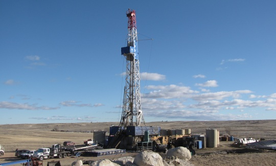 A tall metal tower, which is part of an oil and gas drilling rig, stands on a grassy plain in Wyoming.