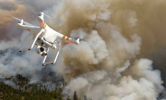 A drone flies over a blanket of smoke.