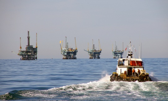 Four large offshore drilling platforms rise like metal towers on the ocean horizon with a small boat in the foreground approaching them.