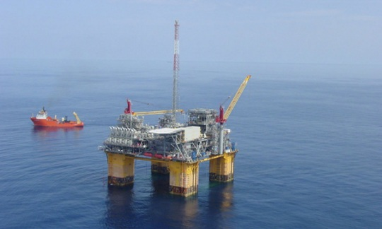 An large offshore drilling platform rises out of the water on four metal legs.
