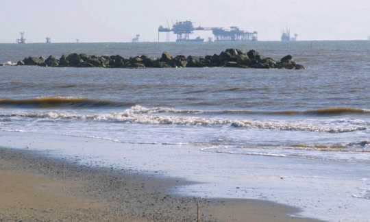The ocean stretches out from a sandy beach with offshore drilling platforms sitting on the horizon.