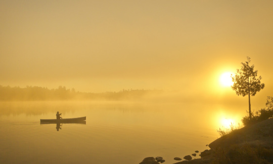 A golden sun shines down on a misty lake with someone paddling a canoe by the rocky lake shore.