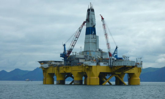 A large oil platform stands in still ocean waters under a gray sky with mountains in the background