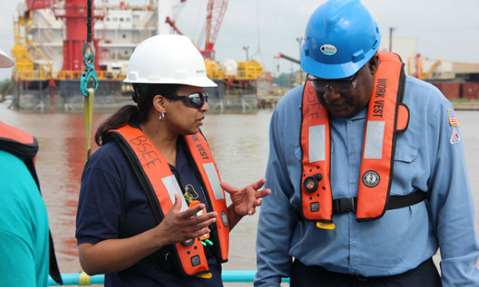 A man wearing an orange life preserver speaks to a woman wearing an orange life preserver and a white helmet with water and oil rig in the background