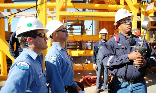 Three men in work clothes and hard hats look at a gauge on a piece of equipment as they stand on a drilling platform made of large metal beams and pipes.