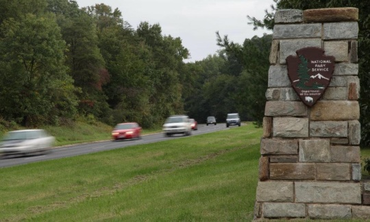 A National Park Service stone sign stands in a grassy median next to a highway with cars driving by.