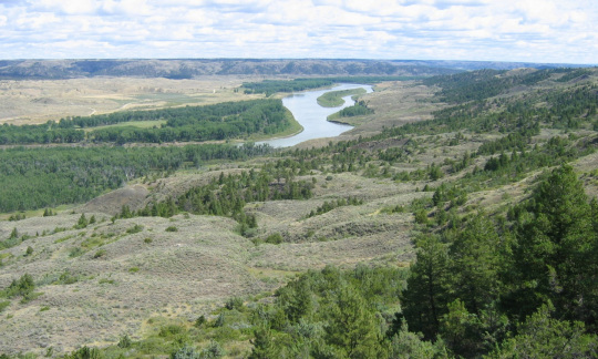 Wide grasslands slope down to a wide river.
