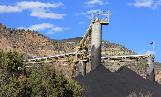In a rugged valley, concrete and steel towers rise above piles of black coal.