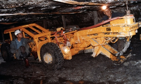 Two coal miners in coveralls and hardhats work with a large piece of machinery drilling into the low ceiling of an underground coal mine.