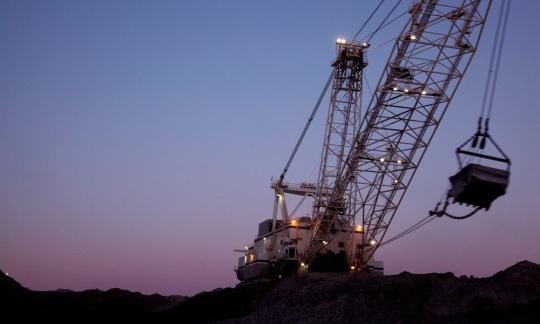 A large crane uses a bucket to lift coal as part of a mining operation.