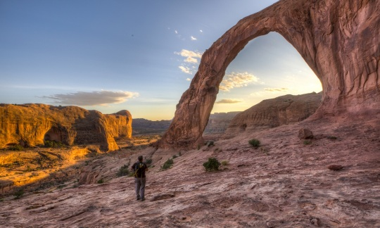 A white man in hiking clothes and a backpack stands on a desert hill looking up at a large natural stone arch with a desert canyon in the background.