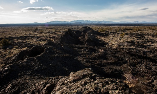 Piles of black rocks are scattered across a wide grassy plain with mountains in the distance and white clouds floating above.