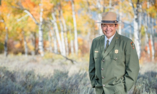 David Vela wears a national park service uniform and hat and stands in a field with trees showing fall colors behind him.