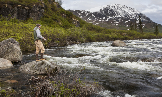 A man in outdoor gear uses a fishing rod to fish in a wide stream flowing through a wide mountain valley.