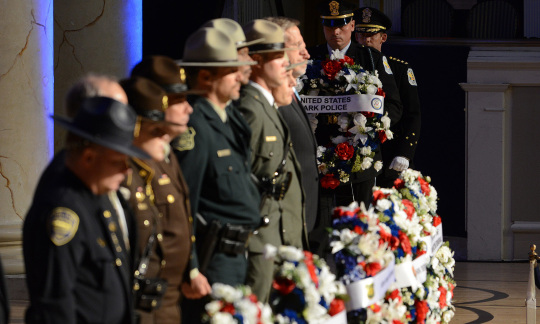 Department of the Interior law enforcement officers stand in a line behind memorial wreaths of flowers on a stage.