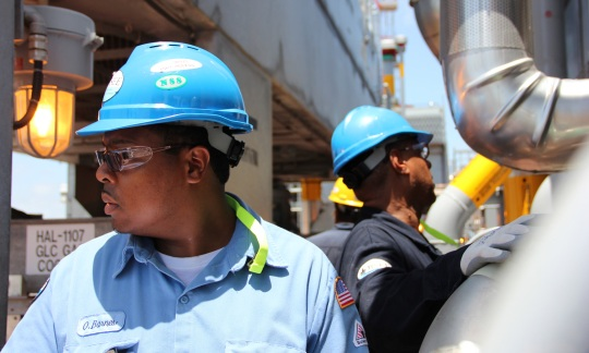 An engineer and inspector dressed in hard hats check equipment on a drilling rig.