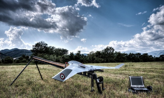 A large metal drone with wide wings sits on a launching ramp in a field.