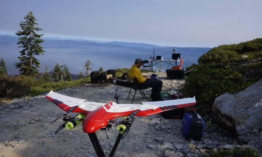 A unmanned aircraft shaped like a small plane rests on a stand next to a man typing on a laptop computer on a hilltop overlooking forests and mountains.