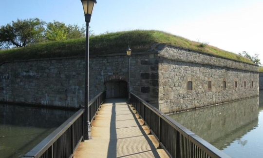 A Footbridge Leads Across A Water Filled Moat To A Door Leading Into A  Large Stone