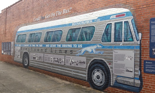 A mural of a grey bus with writing on it is painted on a long brick wall.