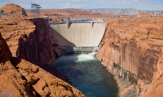 A dam placed on a river between two cliffs of red rock.