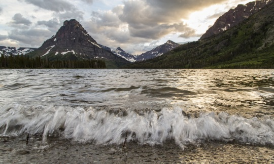 Small waves break onto the shoreline of a lake surrounded by mountains and forests at sunset.