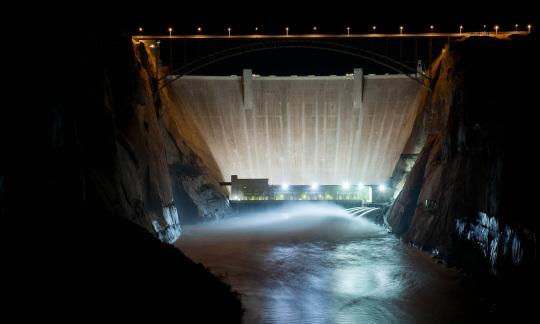Spotlights shine on a massive concrete dam filling up a narrow canyon.