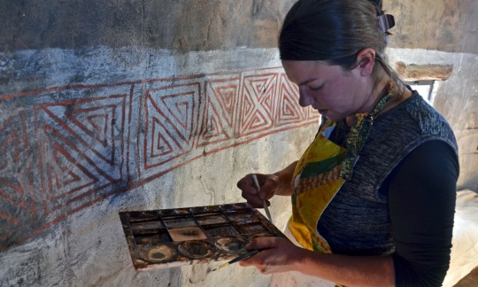 A woman with brown hair wearing a smock uses paint to touch up a native american design on an indoor wall.