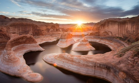 The sun shines down on a twisty, curvy canyon filled with dark water.