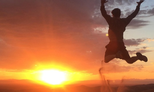 Man Jumping Off Star Dune at Sunset