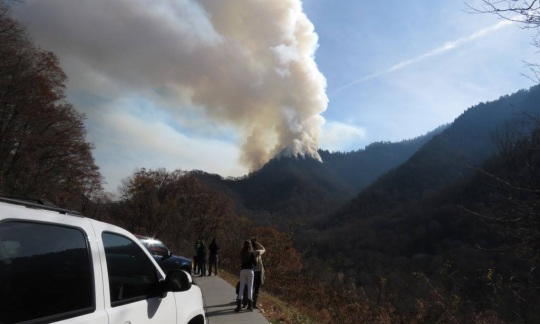 People stand on a road by a parked truck and watch a fire burning on a distant mountain top send smoke up into the sky.