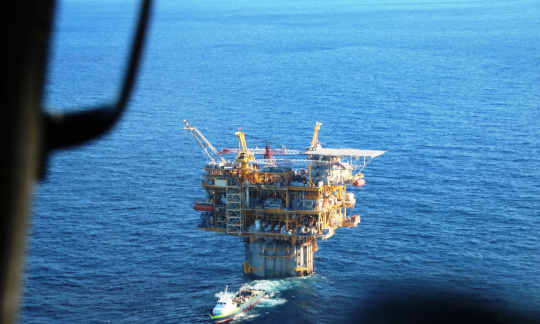 A view from a helicopter looking down at a large metal oil and gas platform rising out of the blue water of the ocean.