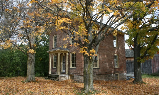 A square, two-story brick house with a small front porch and a barn in the back stands among trees draped in autumn leaves.