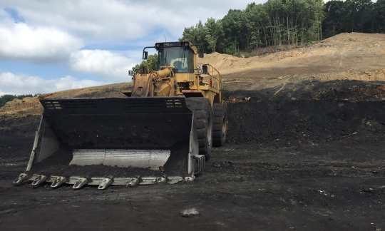 A backhoe loader in front of a pile of coal