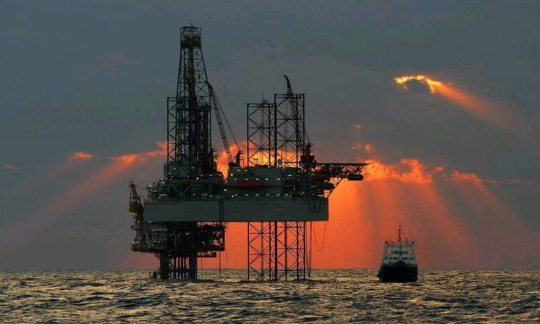Offshore drilling rig, sunset behind the rig