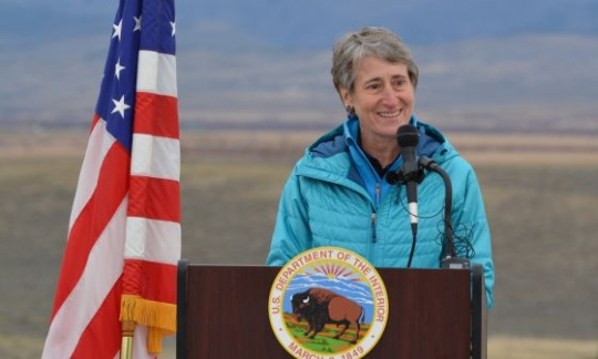 Secretary Jewell stands at a podium next to an American flag