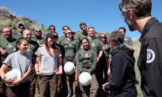A group of young volunteers hold their helmets in their hands while standing outside, smiling and listening to Secretary Jewell.