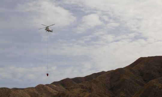 A helicopter flies above mountains